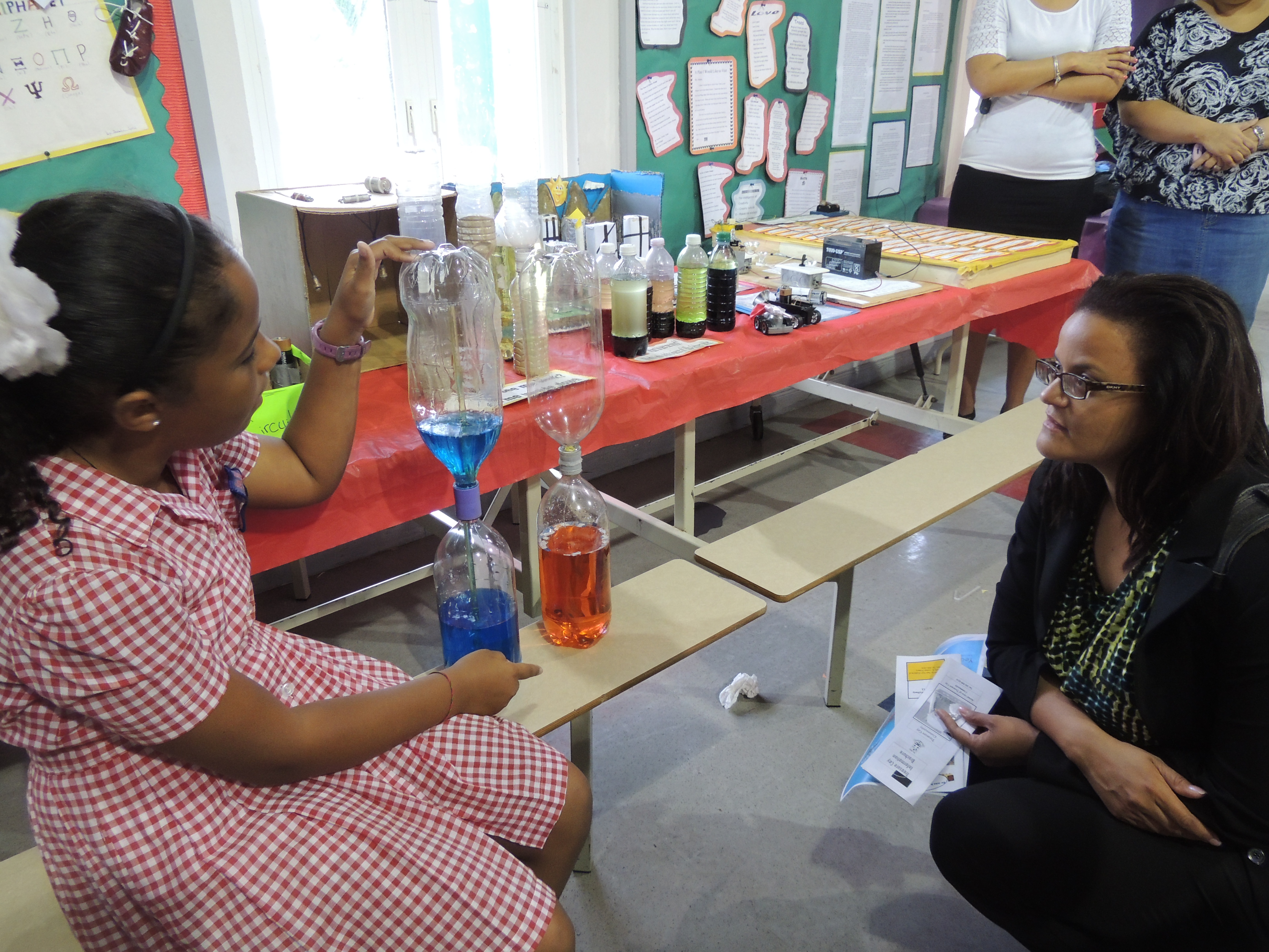 A student shows Minister Rivers her experiment.