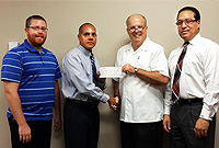 Minister of Finance, the Hon. Marco Archer receives a cheque from Pastor Dennis McCoy on behalf of the Wesleyan Holiness Church to return remaining funds received as grant from the Nation Building Fund, with the Premier, the Hon. Alden McLaughlin, MBE, JP (1 R) and WHC Assistant Pastor Aaron Wetherald.