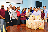 Department of Community Rehabilitation Director, Mrs. Teresa Echenique-Bowen receives a brown paper bagged lunch from Rotaract Club of Grand Cayman President Stephanie Rattan, at DCR offices. Attendees include Rotary District Governor Paul Brown and Ministry of Home Affairs Chief Officer Eric Bush.