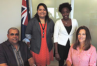 Hon. Minister Osbourne Bodden, Deputy Chief Officer Nancy Barnard seen with interns Lucille Williams-Fernandez (standing: left) and Taylor Clarke-Wint (standing: right).