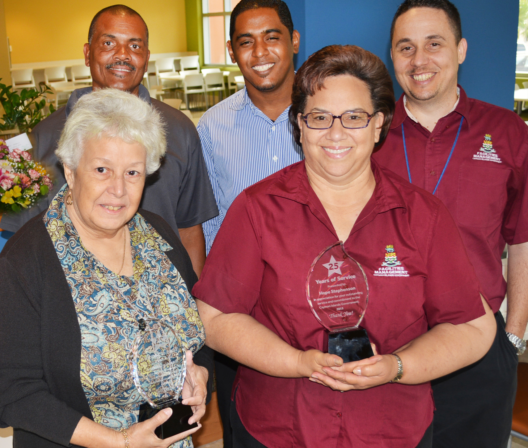 Ms Beatrice (left) and Ms Hope, with their 25-year service awards, are seen with (back row, from left) Mr. Fisher 'Porter' Wright, Mr. Troy Whorms and Mr. Adam McLaren, staff members of the Facilities Management Department, which oversees GAB and other government properties.