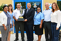 Deputy Governor Franz Manderson presents Acting Chief Immigration Officer Gary Wong the trophy for the government department with the largest number of participants, an honour that the Immigration Department has bagged two years in a row.