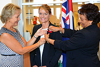 Veterans' daughters Mrs. Kathy Frazier and Mrs. Deborah Ebanks pin Her Excellency the Governor, Mrs. Helen Kilpatrick, the first poppy from this year's Cayman Islands Veterans Association poppy appeal.