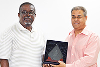 Assistant Customs Collector Trevor Williams receives a retirement plaque from Customs Collector Charles Clifford.
