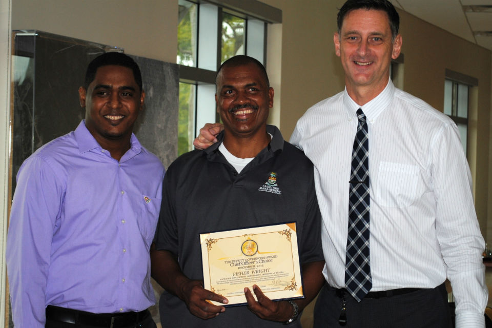 Facility Manager Troy Whorms(Left)  and Chief Officer of the Ministry (PLAHI) Alan Jones (right) flanked Mr. Wright during the award's presentation.