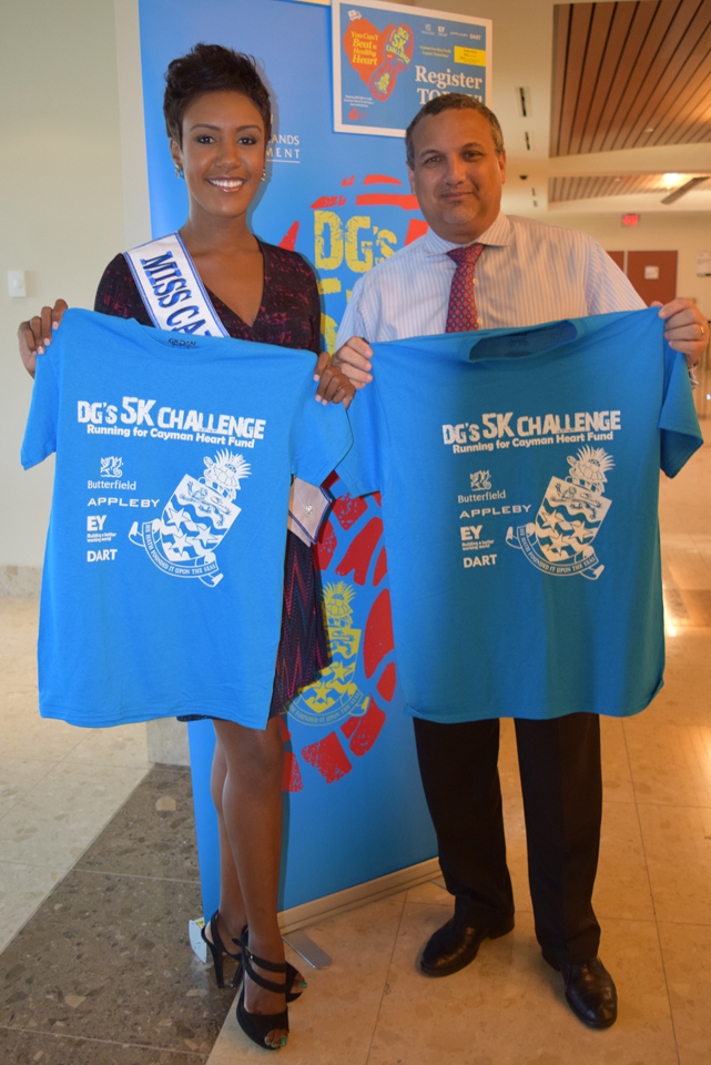Deputy Governor Franz Manderson and Miss Cayman Islands Monyque Brooks with their t-shirts at registration.