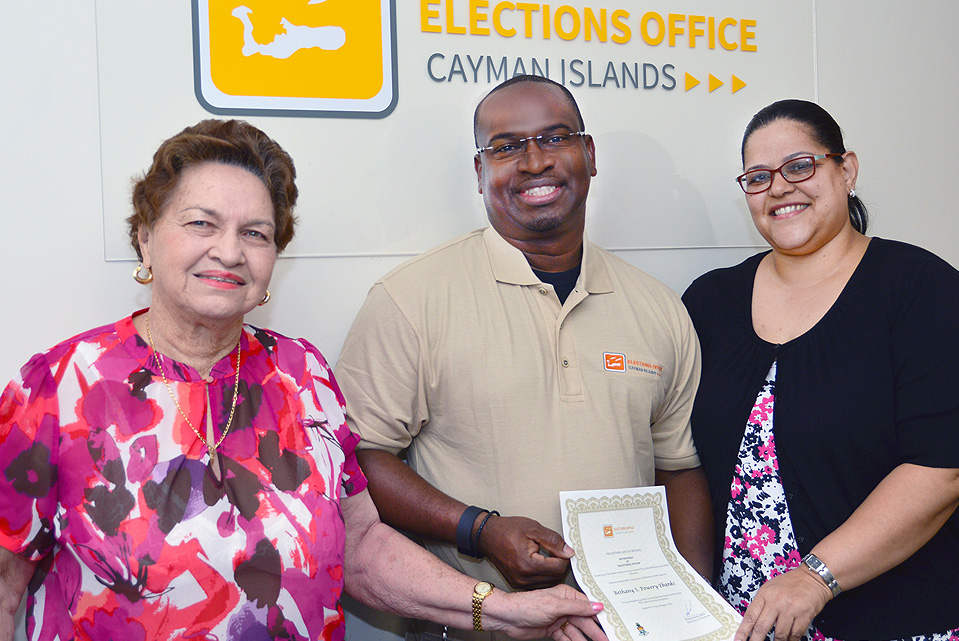 Election Supervisor Wesley Howell (centre) at the hand-over of office from former Elections Registering Officer for West Bay Ms Darlene Owens-Elliott (left) to new West Bay Elections Registering Officer Ms Bethany Powery-Ebanks.