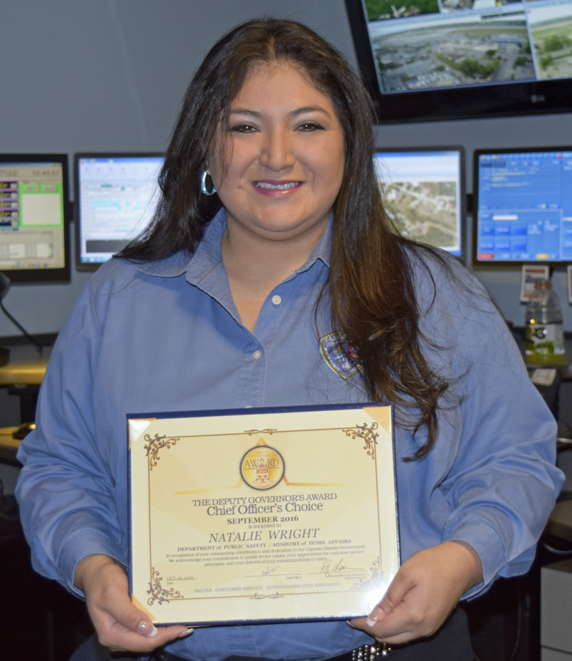 The Ministry of Home Affairs rewards 911 dispatcher Natalie Wright for her lifesaving efforts.