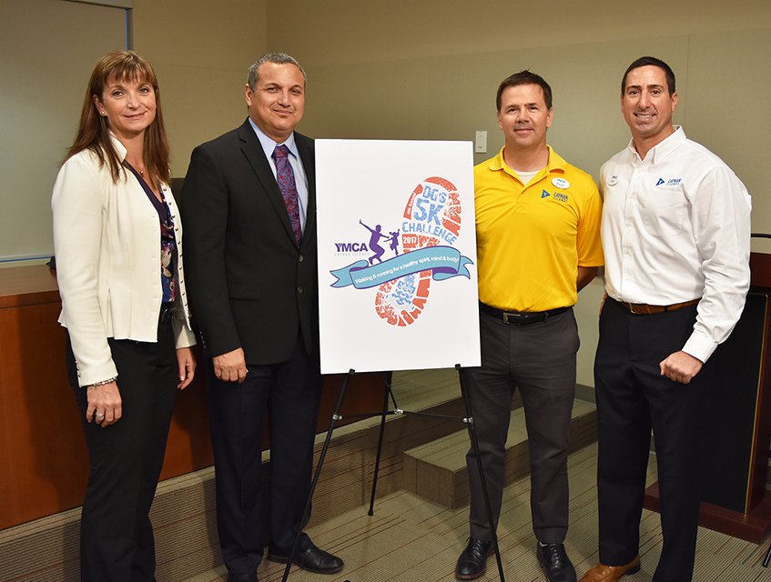 DG's 5K Challenge Co-Chair Jennifer Ahearn, Deputy Governor Franz Manderson, YMCA Deputy Chairman David Watler and YMCA Executive Director Gregory Smith with the 2017 logo.