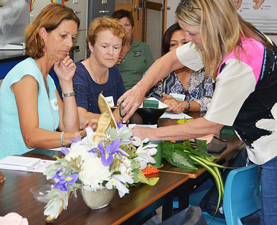 Participants in a recent floral arranging course organized by the Department of Agriculture look on as Debra Ketter, of The Ritz Carlton, demonstrates a technique. Entrants will display their skills in a floral arranging competition on Ash Wednesday.