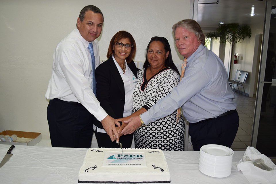 Acting Governor Franz Manderson, PSPB Managing Director Jewel Evans Lindsey, Speaker of Legislative Assembly and Deputy Premier Moses Kirkconnell cut the fund's anniversary cake.