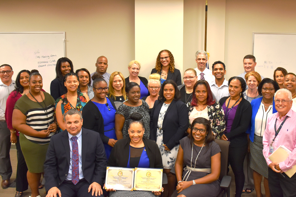 The POCS team celebrates with Employee of the Month Kimberley Powell-Herrera, who is seated centre front with Deputy Governor Franz Manderson and Chief Officer Gloria McField-Nixon