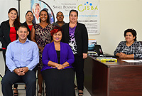 Commerce, Planning and Infrastructure Minister, Hon. Joey Hew with CISBA and ministry officials: seated, L-R: Minister Hew, CISBA President Ms Dawn McLean-Sawney and Assistant Director of Membership, Ms Cheryl Al-Masri at her desk; standing, L-R: Ministry Policy Advisor, Ms Thais Ducent; Deputy Chief Officer, Ms Leyda Nicholson-Makasare, CISBA Secretary, Ms Gina Lawrence, Membership Director, Ms Antoleen Williams and Deputy Chief Officer, Ms Tamara Ebanks; not present were CISBA's Vice President, Ms Glenda Dilbert-Davis, Treasurer, Mr. Omar Chambers and Director of Marketing, Ms Rosa Harris