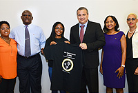 Student Erika Sobers of St. Ignatius School presents Deputy Governor Hon. Franz Manderson a t-shirt that she designed for the Optimist Club of Grand Cayman's ongoing childhood cancer awareness drive. L-r: Erika's mother Mrs. Fay Skeete-Sobers, Optimist Club Vice President, Mr. Fred Dallas, Erika Sobers, Deputy Governor, Hon. Franz Manderson, club President, Ms Elaine Harris and club member Ms Gail Bell.