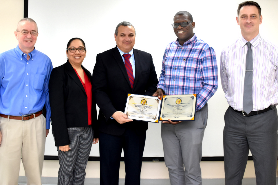 Levi Allen, Employee of the Month for January 2018, receives his certificates from Deputy Governor Franz Manderson and Chief Officer Alan Jones. Also pictured are PWD Director Max Jones and Leyda Nicholson-Makasare, Deputy Chief Officer in the Ministry of Commerce, Planning & Infrastructure.