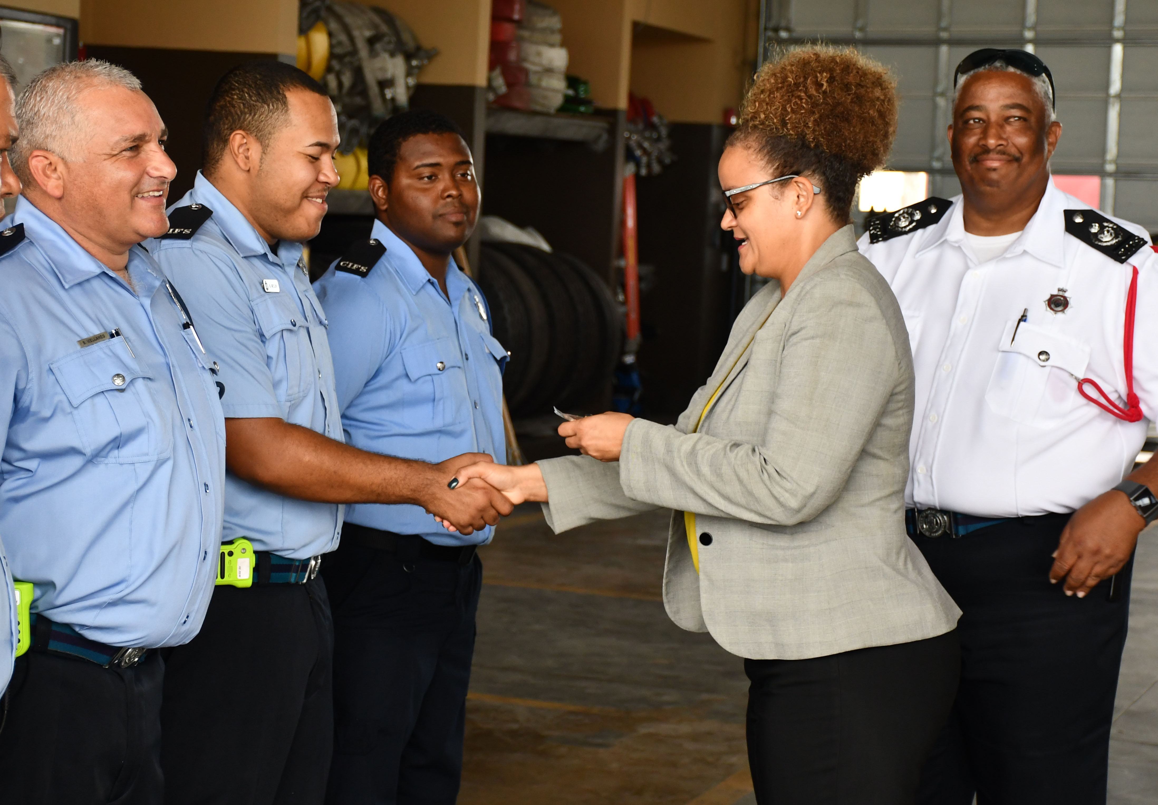 Minister Rivers presents fire officers with their challenge coins.