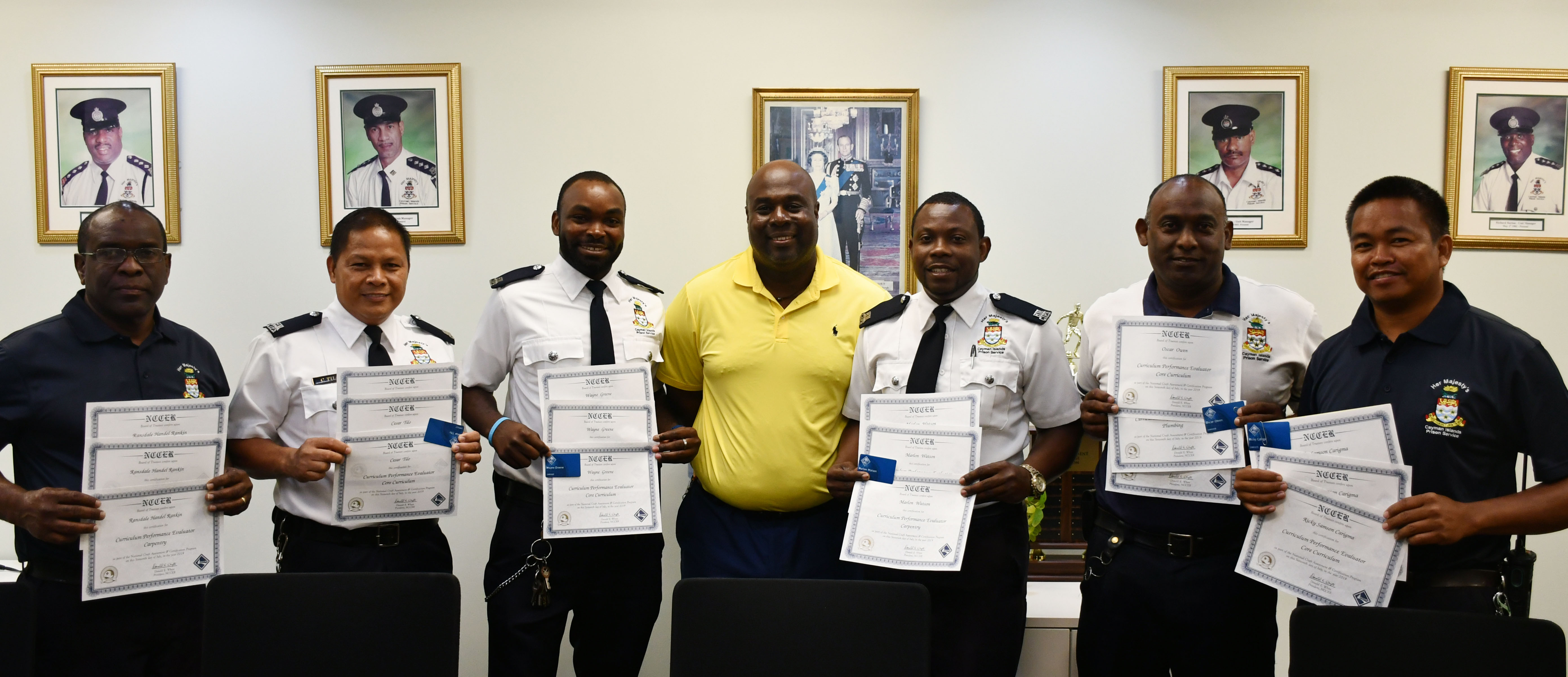 Prison Officers Ransdale Rankin, Cesar Tilo, Wayne Greene, Marlon Watson, Oscar Owen, Ricky Carigma (left to right) receive their training accreditation certificates from Inspire Cayman's Director Michael Myles (centre in yellow).