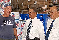 Minister of Tourism, Environment, Investment and Commerce, the Hon. Charles Clifford talks with Caybrew General Manager Allen Chu Fook (right) and Hank Ebanks (second left) of the beer company's packaging department while touring its Red Bay plant recently.
