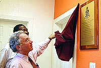 The Governor unveils the plaque to officially open the education centre, accompanied by Prison Director Dwight Scott.