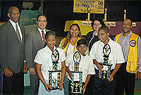 (Front row) Spelling champion Venkatta Batta (centre) with Moesha Ramsay-Howell (left) and Joshua Dilbert.  Standing behind the winners are (left to right) Mr Joseph Biggs of British American Insurance; Education Minister, the Hon. Alden McLaughlin; Lion Natasha Bodden; Chief Education Officer Shirley Wahler; and Lions President Anthony Ritch.