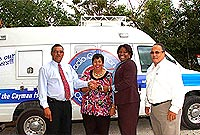 Minister of Communications, Works and Infrastructure, the Hon. Arden McLean, JP (left), presents the keys for a new remote-broadcast van to Radio Cayman Director Norma McField (third left). Looking on are Radio Cayman's Acting Deputy Director and Sales and Promotions Manager Paulette Conolly-Bailey (centre), and Ministry Chief Officer Carson Ebanks, MBE, JP.