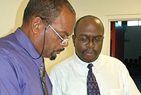 Studying nomination documents, Deputy Supervisor of Elections Colford (l) and a Returning Officer for George Town Philip Barnes (r).