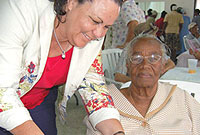 Ministry of Health and Human Service Chief Officer Diane Montoya serves lunch to Mrs Glen Ebanks (87) of North Side.