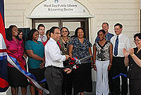Minister Alden McLaughlin cuts the ribbon, assisted by Chief Education Officer Shirley Wahler (R).