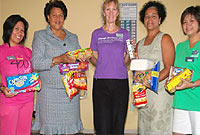 DCFS Director Deanna Lookloy (second from left) and DCFS Disaster Coordinator Lynda Mitchell (fourth from left) accept donations from Curves' Diane Musselwhite, accompanied by staff members Love Giyangan (left) and Mia Cruz.
