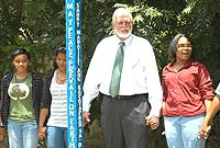 Minister of Community Affairs and Housing the Hon. Mike Adam, MBE with students at the unveiling of Cayman's first peace pole at in George Town's Dart Park. (Left-Right) Ana Olson, Megan Ebanks, Minister Adam, and Jenna Munruddin.
