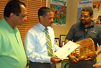 Health Minister the Hon. Mark Scotland congratulates Public Health staff on their award. From left to right: Medical Officer of Health Dr. Kiran Kumar, Minister Scotland and Public Health Surveillance Officer Timothy McLaughlin.