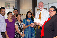 Minister for Community Affairs and Housing the Hon. Mike Adam, MBE, receives a donation of CI$1,500 from the Indian Association of the Cayman Islands members. From left: Association member Lenin Perumalsamy; Treasurer Rashmi Arun, Director Alexander Rodrigues, member Dr. Cicely Abraham, President Bina Mani, Minister Adam and DCFS Deputy Director Alicia