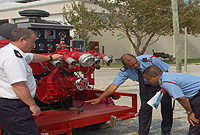 Fire Officer Brainard McLaughlin (2nd left) makes a presentation during a recent Cayman Islands Fire Service train-the-trainer workshop. Lancashire Fire and Rescue Service Training Officer Paul Rose (left) is among those looking on.