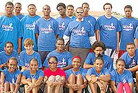 Minister of Sports the Hon. Mark Scotland, JP (standing, wearing sunglasses), along with ministry officials and Cayman's star athlete Cydonie Mothersill (seated, wearing sunglasses), meets members of Cayman's CARIFTA 2010 team.