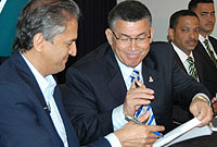 (L-R) Dr. Devi Shetty and the Hon. Premier McKeeva Bush, OBE, JP, sign the agreement.