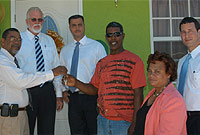 New homeowner Rupert Cole receives his keys from National Housing Development Trust (NHDT) Chairman Steve McLaughlin and Housing Minister the Hon. Mike Adam.  Others left to right are: Mr. Cole; Mr. McLaughlin; MLA and Ministry Housing Councillor Ellio Solomon, JP; Ministry Chief Officer Dorine Whittaker; and NHDT Board Member Rayal Bodden.