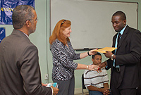 University College of the Cayman Islands (UCCI) Board of Governors Chairperson Berna Cummins (centre) congratulates first year business administration major Winston Williams on completing the Men of Standard programme. UCCI President Roy Bodden (left) and participant Jonathan Jackson (seated) look on.