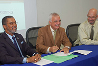 Island Heritage Chief Operating Officer Hugo Cardona (centre) signs on the dotted line as University College of the Cayman Islands President Roy Bodden (left) and Dean Brian Chapell look on.