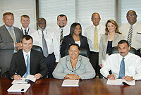 Officials at the signing (sitting L-R) Icon Institute's Head of Unit Holger Hinterthur; Deputy Premier Juliana O'Connor-Connolly MBE, JP, and Cayman Islands Airports Authority Chief Executive Officer Jeremy Jackson. Standing (L-R) are Icon Institute's Engineer Gunter Schieske; Administrative Officer 1 David Fawcitt; Cabinet Secretary Orrett Connor MBE, JP, Chief Meteorologist John Tibbetts; Senior Assistant Financial Secretary Anne Owen; Chief Officer Kearney Gomez; Policy Analyst Christina Rowlandson; and the Cayman Islands National Weather Service Director General Fred Sambula.