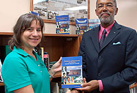 Archivist Tricia Bodden (left) accepts a copy of Roy Bodden's Patronage, Personalities and Parties: Caymanian Politics from 1915-2000 on CINA's behalf. The book is now part of CINA's reference library.