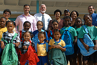 After presentations to DCFS clients, government officials and Foster's Food Fair IGA Manager and staff hand over school bags to primary school students, beginning with George Town Primary.