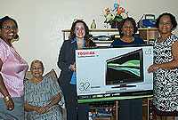 Cayman National representatives gift Sunrise Cottage residents with a television. (L-R) DCFS Adult Care Coordinator Dawn Rankine; Sunrise Cottage resident Erna McKoy; CNB Executive Assistant Christy Braggs; Cayman National's  Corporate Communications Senior Executive Claudia Welds; DCFS Disaster Services Coordinator Lynda Mitchell and Sunrise staffer Marcia Gayle.