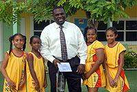 Bodden Town Primary netballers (from left) Maria Lewis, Iyanla Solomon, Yvonne Solomon, and Athena Smith present gifts to Bodden Town MLA Dwayne Seymour, in thanks for a $1,100 donation that he and Sports Minister Mark Scotland made to their team.