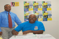 Busy reconciling numbers are Deputy Census Manager Crispin Boney and Area Coordinator Selburn Christian.