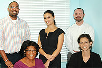 Commissions Secretariat Manager Deborah Bodden (seated at right) and Office Administrator Doralyn Stewart. Standing (L-R) are analysts Jason Webster, Josephine Hislop and Michael Ebanks.