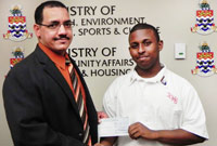 Minister of Education, Training & Employment, the Hon. Rolston Anglin, JP (left) presenting a $3,000 sponsorship cheque to John Gray High School Deputy Head Boy Nijel Powery. Nijel is one of three John Gray students who will be attending the prestigious Global Young Leaders Conference in Washington, D.C. and New York City.