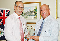 (L-R) Acting Governor the Hon. Donovan Ebanks, MBE, JP, presents an award to District Commissioner Ernie Scott, JP.