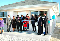 Government officials and National Housing Development Trust representatives cut the ribbon to the first of 12 affordable homes in East End.