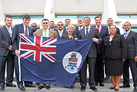 Premier the Hon. W. McKeeva Bush presents an official Cayman Islands National flag to UK MPs Mr. Andrew Rosindell (fifth from right)' Mr. Brian Donohoe (second from left) and Mr. Graham Brady (fourth from right).