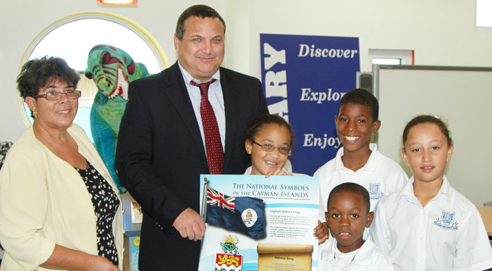 (L-R) George Town Primary School's Principal Marie Martin and Deputy Governor the Hon. Franz Manderson, Cert. Hon., with students Makeda Harris, Amare Hamilton, Joshua O'Garro and Hannah Newball, with the new Cayman Islands National Symbols poster.